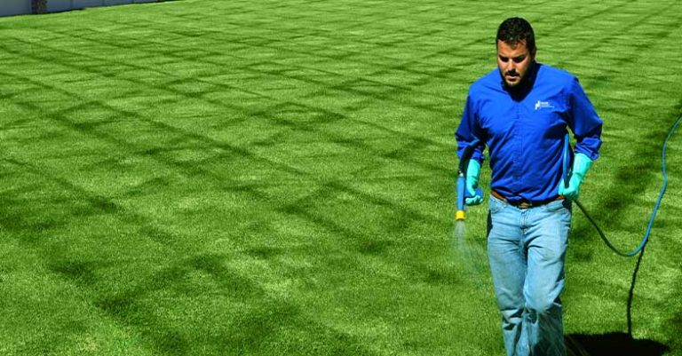 Holmes Lawn & Pest employee applying 6th round of fertilizer on a lawn in Salt Lake City, Utah