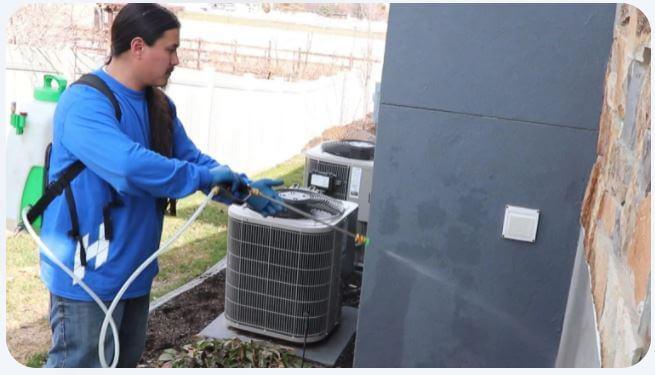 Holmes Lawn & Pest Employee spraying pest control on a house in Salt Lake City, Utah